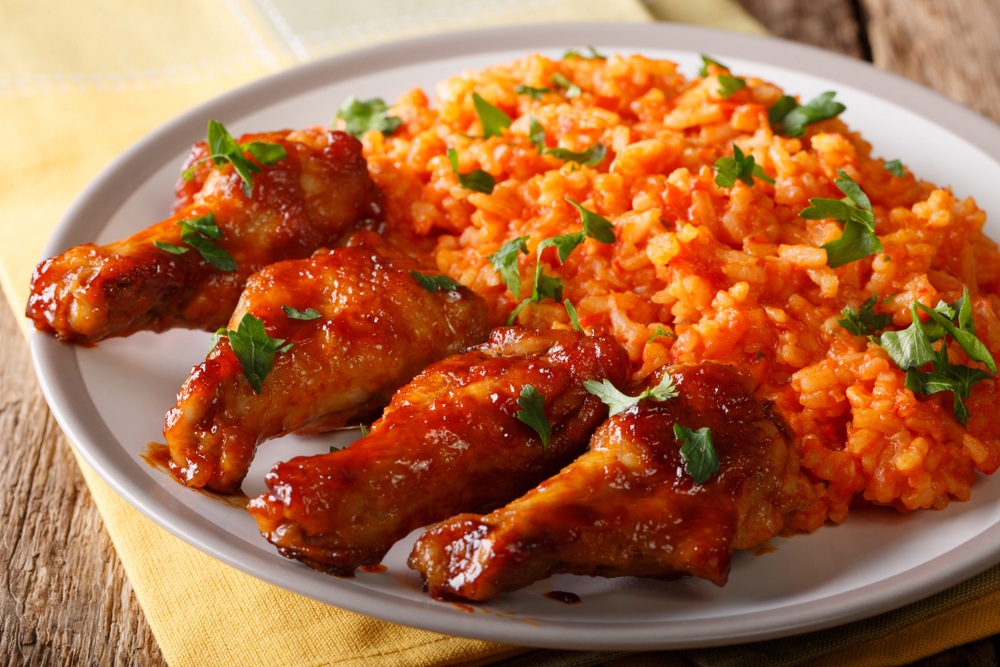 Nigeria - Nigerian food party: Jollof rice with fried chicken wings close-up on a plate. horizontal
