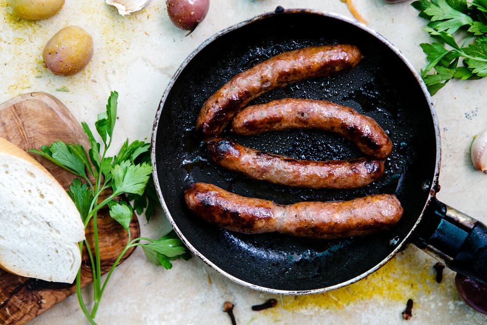 Tunisie - Cuisine tunisienne - saucisses grillées, merguez dans une poêle, aux olives, baguette et épices, vue du dessus