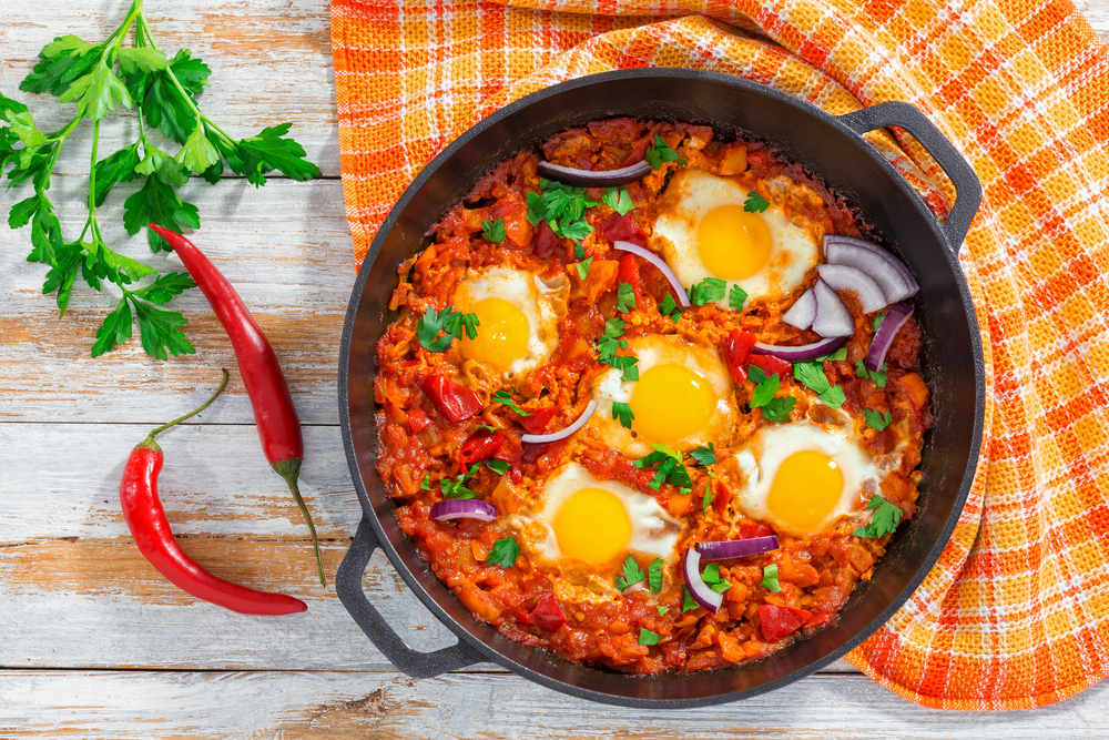 Tunisia - Tunisian Food - healthy breakfast shakshuka - fried eggs, onion, bell pepper, tomatoes, chili and spices in iron pan with kitchen towel, parsley on white wooden planks, authentic recipe, view from above