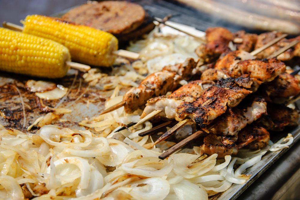 South African Food - Barbecued chicken kebabs on skewers, corn on the cob and onions