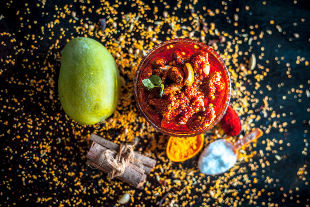 Popular Indian & Asian pickle of mango in a glass bowl i.e. Aam ka achar in a glass bowl or keri ka achar with its entire raw ingredients including spices and mango on black colored shiny surface.