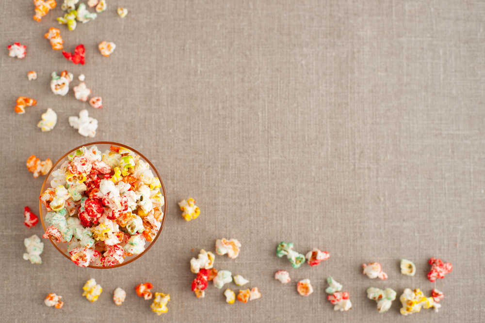 South African Food - Colorful popcorn on a background of burlap. Popcorn is scattered in the corner of the background. Popcorn is in the cup. Popcorn can be seen from above.